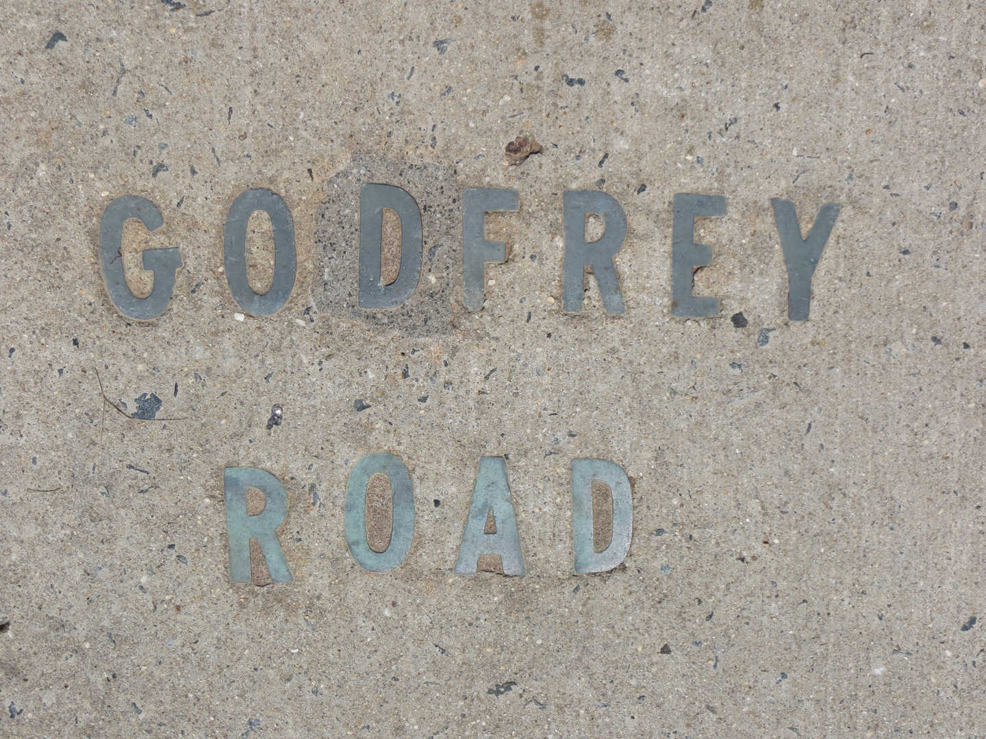 Bronze letters inserted into the sidewalk spelling out Godfrey Road at the southwest intersection of Godfrey and Edgemont Roads. May 2013.