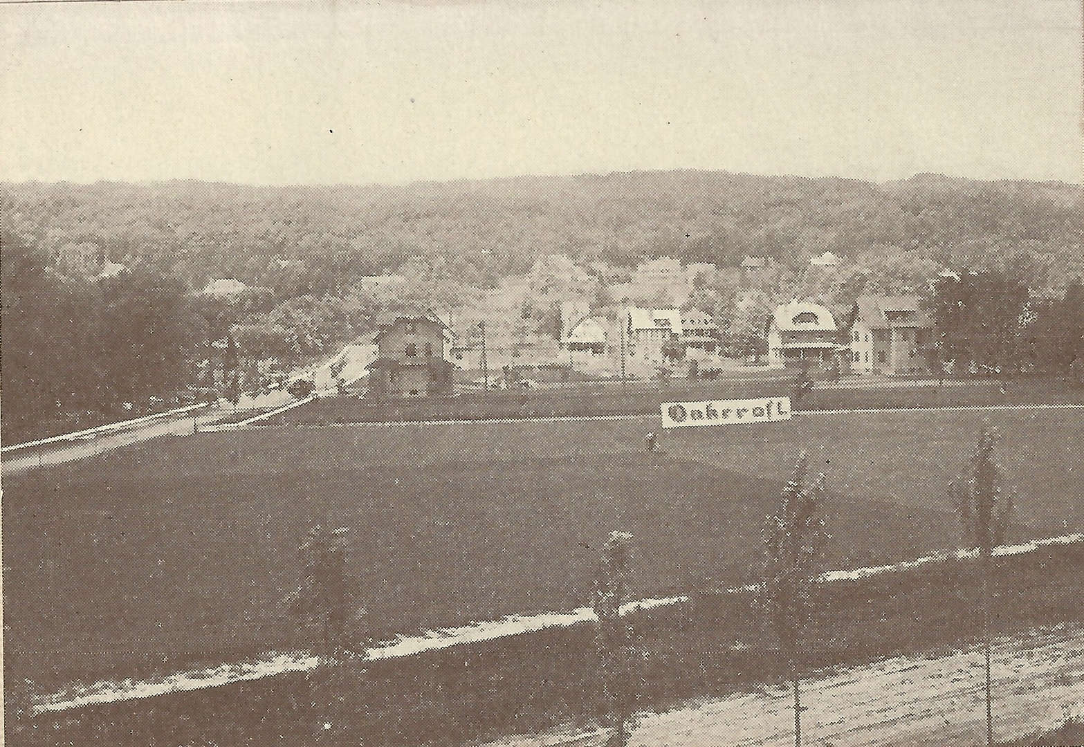 Oakcroft in its early days, looking west from the train tracks, with a sign heralding the subdivision. From the Oakcroft sales brochure, circa 1908.