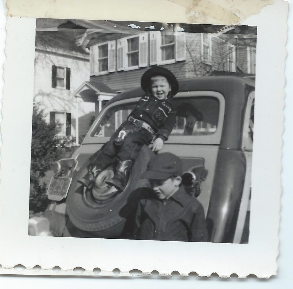 Old photo of two young boys posing on a car